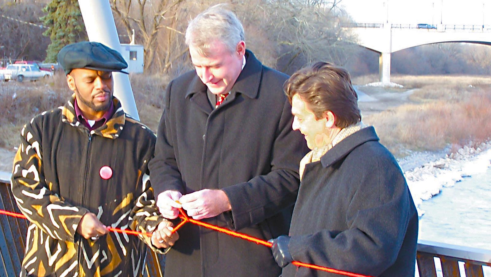 Black and white alderpeople tie ribbon on North Avenue Dam pedestrian bridge with Milwaukee Mayor Tom Barrett