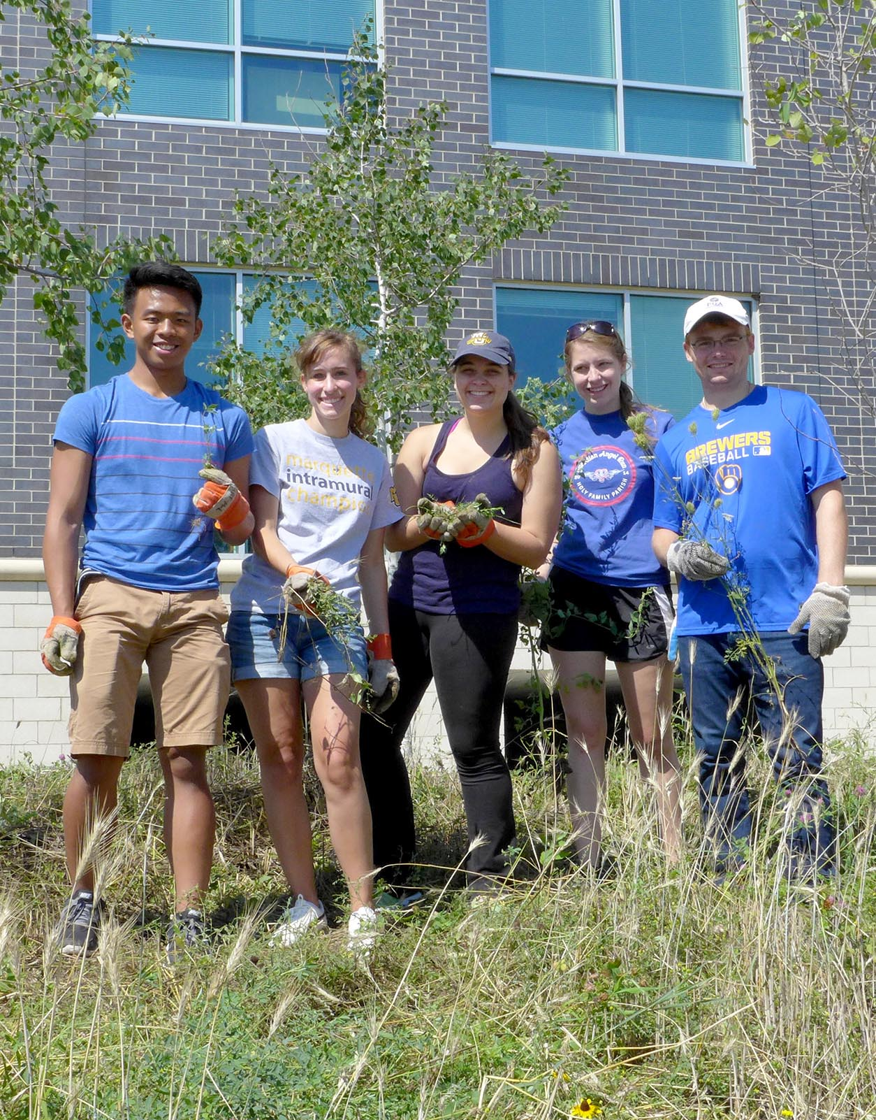 5 college volunteers from Marquette University standing in a line with the invasive plants they removed