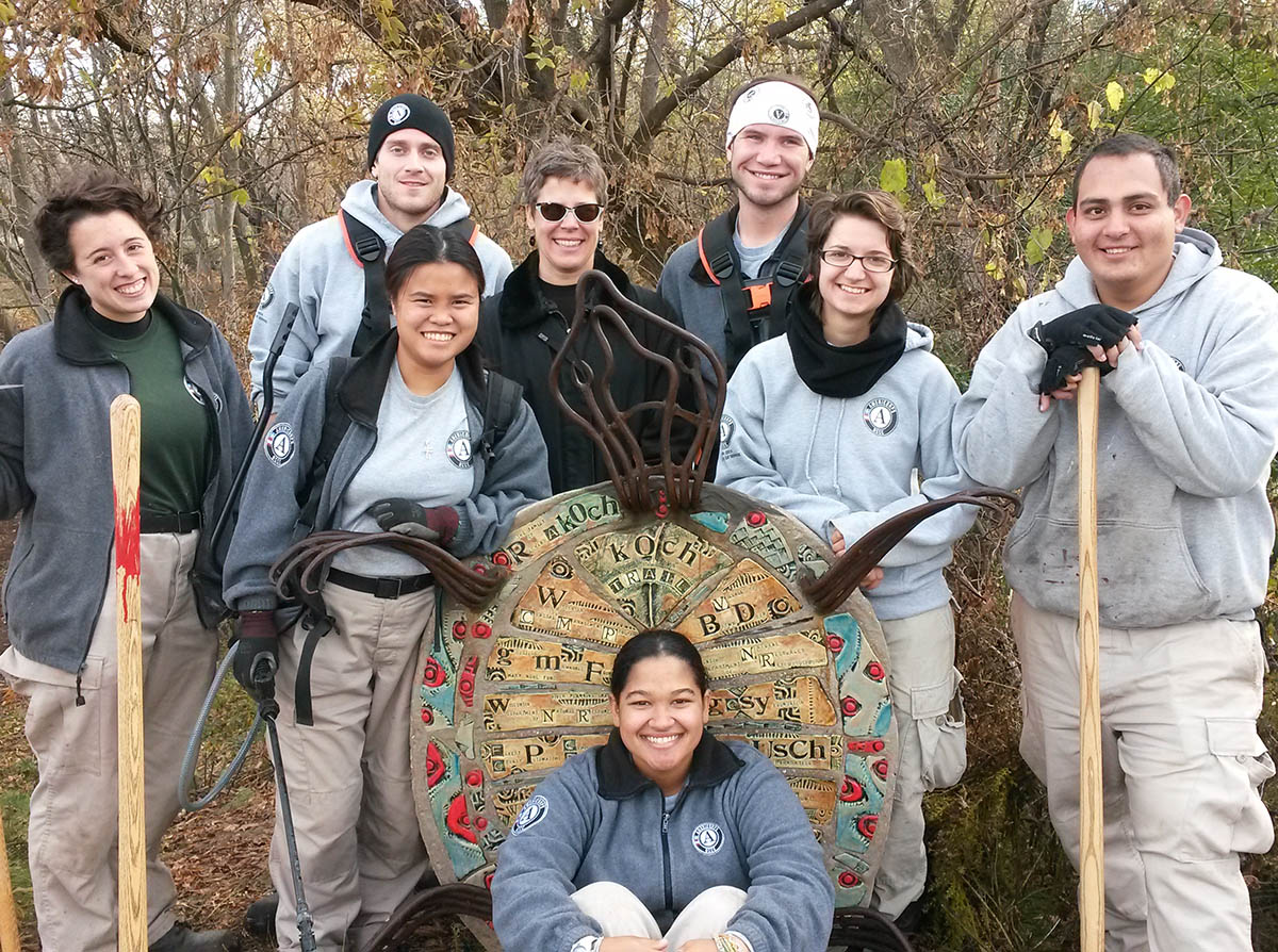 Americorps volunteers stand around the Koch Woodlands turtle sculpture