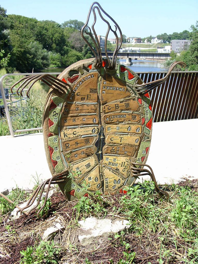 A turtle sculpture that lists the funders for the East Bank Trail