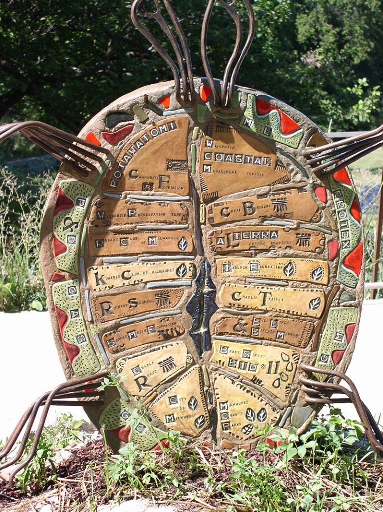 A close-up of a turtle sculpture that lists the funders for the East Bank Trail