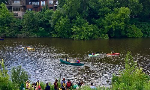 people paddling in the river on canoes and kayaks