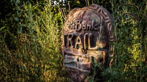 A sign that says East Bank Trail shines in the sun